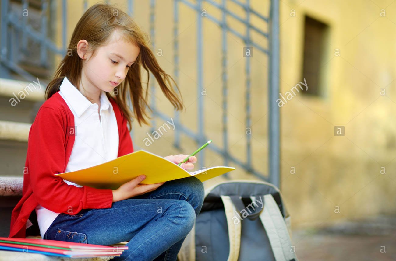 adorable-little-schoolgirl-studying-outdoors-on-bright-autumn-day-young-student-doing-her-homework-education-for-small-kids-back-to-school-concept-P92D2X